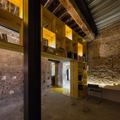 Photo byFernando Alda. Cool Officespace! Old and new combinated and yellow-concrete-shapingshelfs. So rad!