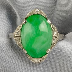 Art Deco Platinum, Jadeite, and Diamond Ring, set with a cabochon jadeite measuring approx. 14.50 x 11.00 x 5.85 mm, old single-cut diamond melee accents, and garland-engraved shoulders