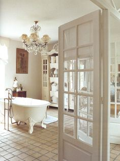 Now this is a Bathroom to die for! I love the French Doors, the Chandellier, the Gorgeous Armoire/Shelves... What a Big, Beautiful, Simple yet Elegant Space. I love it.