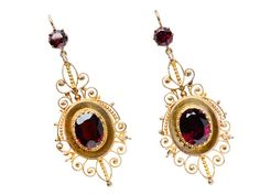 Outstanding Almandine Garnet Earrings. Glorious wire work provides an arresting and striking interpretation of the fabulous design work of mid-Victorian jewelry. The earrings demonstrate a superb use of deep purple merlot tinted almandine garnets and 14k yellow gold.  Round faceted garnets (.70 and .74 carats) support a tiered element of superbly crafted golden spirals, scrolls and orbs appointing a round medallion centered with oval faceted almadine garnets (3.6 and 2.25 carats) centered…