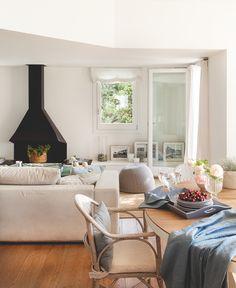 Salón con comedor. La chimenea es  un diseño de Coderch. Alfombra a medida de Pere Batalle. Cojines del sofá de Filocolore y del comedor, de Matèria.
