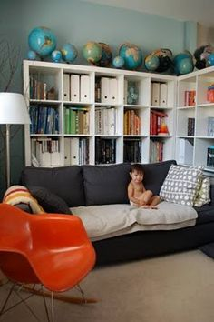 Why not place your IKEA bookcase behind the sofa? You can stash those rarely used or unsightly items behind it. Brill!