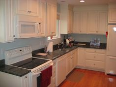 Classic white kitchen cabinets with dark granite counter-tops and white appliances.