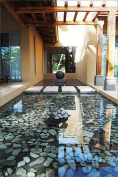 Architectural reflection pool with wood arbor and rectangular concrete stepping stone pavers