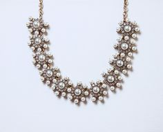 """A row of gorgeous pearls and crystals line this statement necklace and make it a Holiday piece to remember. With their snowflake-like shape, these """"bursts"""" of beads will keep you in the holiday spirit"""