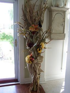 Okay, so put the burlap ribbon, fall flowers, and corn stalks all together ~