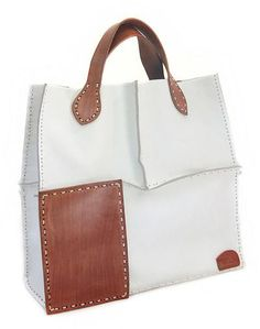Nanan's trendy design exudes urban chic with a touch of safari vogue. The #leather #bag is tooled by hand featuring contrasting panels. These are placed on the top or the bottom of either side. Sturdy handles in the same shade complete the bag's refined allure.