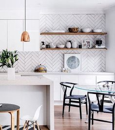 Une cuisine immaculée et son carrelage mural géométrique