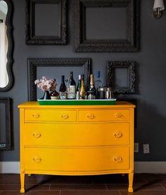 peinture pour meuble, commode jaune vintage avec un mur de fond gris anthracite décoré de cadres noirs