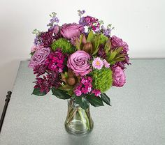 MOTHERS DAY BOUQUET. Parisian Sunset Bouquet. Show Mom you love her with this beautiful, beguiling mix of colors and flower forms. Sophisticated tones of purple and green combine in this blend of lavender Roses, cone-like green Leucadendron, fuzzy green Dianthus, small pink Asters, and purple Mums and Stock. An excellent way to delight Mom on Mother's Day.