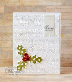 Sheet Music embossing folder on white card stock creates an elegant background to this simple handmade Christmas card.  Die-cut holly leaves with sparkly sequins in red and white are great pops of color.
