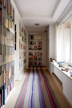 Be still my heart... A wall of books and another of windows...YES! ~ (Although my practical side is telling me you would have to watch the sunlight on the books' spines or they would soon be faded and deteriorated... there has to be a good work around cause I love this passageway!)