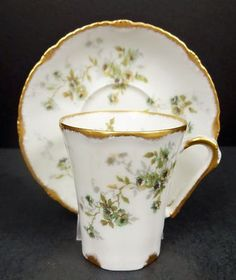 This porcelain chocolate cup and saucer was produced in France by Theodore Haviland Limoges in the late 19th century. The saucer has a diameter of 4 5/8 inches and the cup is 2 3/4 inches high. The s