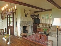 This room is way past perfection! Amazing fireplace, the antlers, beautiful rug, incredible iron chandelier, beautiful table.  Great cozy farmhouse style.   timthumb.php (980×735)