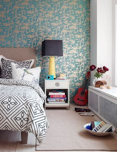 Mark Lund Photography    contemporary bedroom design with turquoise blue & gold metallic wallpaper, gray linen headboard bed, white nightstand, yellow lamp with black shade and white & black geometric bedding duvet and white & black damask pillow.