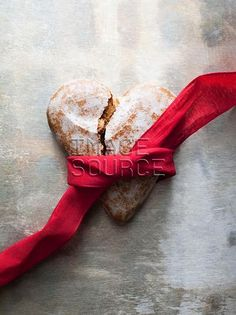 Broken heart-shaped gingerbread cookie with red ribbon