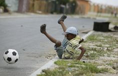 A boy tumbles as he plays soccer on the streets of the Khayelitsha township in Cape Town, December 3, 2009. REUTERS/Kai Pfaffenbach