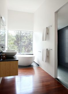 This house's spacious bathroom behind the main bedroom is dominated by a white oval bath