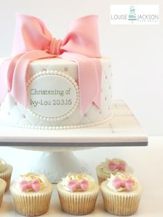 Girls christening cake with large sugar bow, quilted and pearl effect, hand painted name plaque and matching cupcakes
