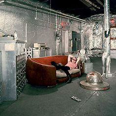 Warhol on the famous red couch in the silver-lined Factory, 1967