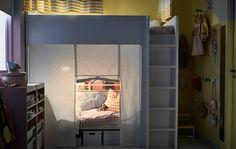 Ein geteiltes Kinderzimmer mit Hochbett, ausziehbarem Bett darunter und mit einem Vorhang um jedes Bett