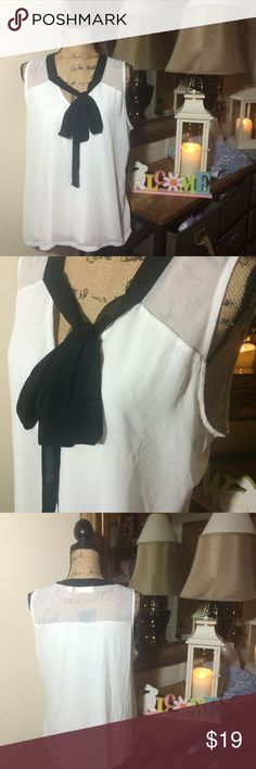 7th Avenue Design Studio White & Black Sleeveless 7th Avenue Design Studio New York & Company White & Black Sleeveless Top; this has dual layers on the front with sheer sleeves & a portion of the back, it also has a black tie on the front...super cute top! It is gently used and in overall good condition; size L New York & Company Tops Blouses