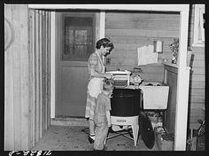 A woman ready to do laundry.  You can see the washer has a wringer at the top that you crank to squeeze excess water from the clothes.  California, 1942