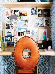 Printed blue wall paper, beige bulletin board with photos, brown leather chair, and wood desk