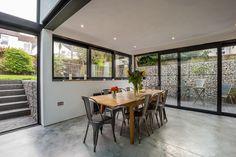 Brighton home | industrial renovation | sliding and bi-fold doors | black aluminium frames | concrete floor finish | feature patio stone wall | garden levels | exposed beams | Sussex |