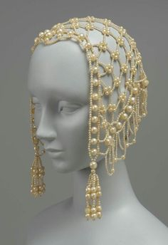 Snoodlike head covering, circa 1850, French. Pearls were brought in large amounts by the French East India Company, and from the pearl centres on the Persian Gulf, to Paris for the wealthy to be fashioned into countless adornments, and copies made of paste for the middle-class.