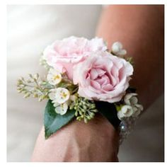 Corsage of light pink spray roses with seeded eucalyptus and waxflowers on a ribbon bracelet