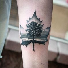 This idea of a black and grey leaf with the Boston or Salem city in it and the tree with orange and yellow foliage blowing in it.