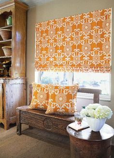 I love the orange fabric shade and matching pillows