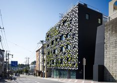 Plants sprout through the patchwork aluminium facade of this pharmacy and clinic in Japan by architects Kengo Kuma and Associates.