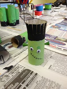 Paint tolet paper roll green and black, snip hair end, use green golf tees for bolts, add google eyes and mouth with black marker