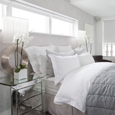 Stylish white bedroom            	 	Blending ice-white walls, bedlinen and roller blinds with cool dove grey accents gives a bedroom a chic, timeless appeal. Mirrored furniture, such as a chest of drawers, reflects light to add depth to the scheme.