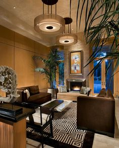 This striking living room boasts a grand fireplace and two luxurious brown velvet sofas. A patterned area rug adds movement and interest underfoot, and two round light fixtures provide a stylish source of light overhead.
