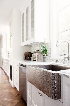 White cabinets and a farmhouse sink in this kitchen