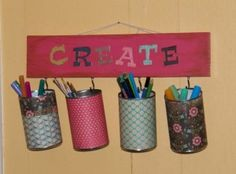 Soup cans drilled with hole in back for J hook and wrapped in scrapbook paper for storing craft items, etc. (could also be hung on a rod with S hooks)