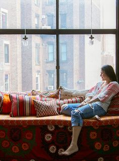 Marika Wagle, one of the homeowners featured in Justina's book, gazes out her Tribeca loft window amid an enviable collection of kilim pillows in a riot of colors.