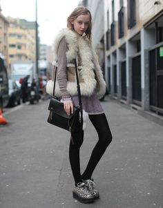 Street Style: This is a cute winter look. The fur is a nice addition, as well as the patterned shoes. I've never worn longer shirts under vests, but this model wears it perfectly.