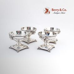 Vintage sterling silver set of 4 open salt dishes having a pedestal with 4 paw form feet. The dishes are decorated with figural ram heads and repousse garland motifs as well as beaded rims. Marked 8058. Made by Shreve & Co. San Francisco, c. 1920.