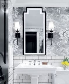 Sophisticated sconces, a stately mirror and subway wall tiles with contrasting grout keep the playful wallpaper from looking too ethereal.   Image: Alex Lukey   Styling: Scott Young   #Bathroom #SmallSpace #BlackandWhite #StyleAtHome