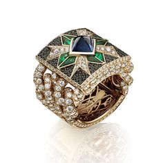 Giampiero Bodino Rosa dei Venti ring set with a central sugarloaf sapphire, emeralds and black diamonds on a diamond-encrusted chain.