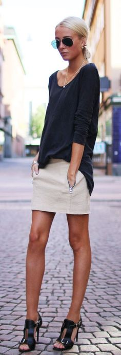 Chic zipper miniskirt, black buckle sandals, loose black top, a simple necklace, and aviator sunglasses