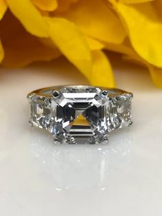 Asscher cut three stone engagement ring, white sapphire in yellow gold Three Stone Engagement Rings, Antique Engagement Rings, Sapphire Stone, White Sapphire, Wedding Ring Styles, Wedding Rings, Beautiful Rings, Diamond Rings, Jewelry Rings