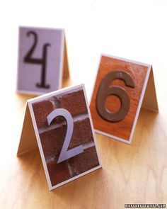 Searching for the perfect table numbers? Look no further than your front door -- and those of your neighbors. Snap digital photos of house numbers, as well as those on awnings and signs.Upload photos to a computer; crop so number fills the frame. For double-sided displays, print two of each digit onto photo paper. To make tented stand, cut two pieces of mat board (ours are 5 3/4 by 3 1/4 inches). Trim photos to be slightly smaller than the boards; center and affix with double-sided tape…