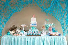 Preciosa la combinación de colores en tonos azules y rosas que se han usado en la decoración de esta fiesta infantil de sirenas y el mar que se celebró en Australia. Para simular la arena se usó azúcar moreno. Las galletas, los cupcakes, la tarta y los macarons tienen una pinta estupenda! Little mermaid