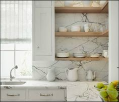 Counter to ceiling marble backsplash with open shelving. Design by Christopher Peacock Home .