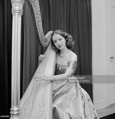 A picture of harpist Jane Greenough holding a harp and posing for the picture, New York, 1947.